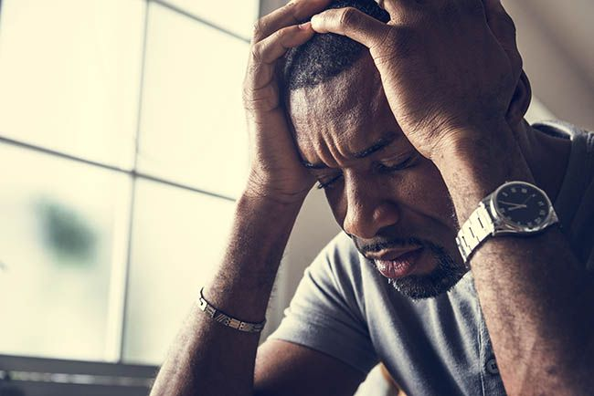 Black man stressing out and having a headache