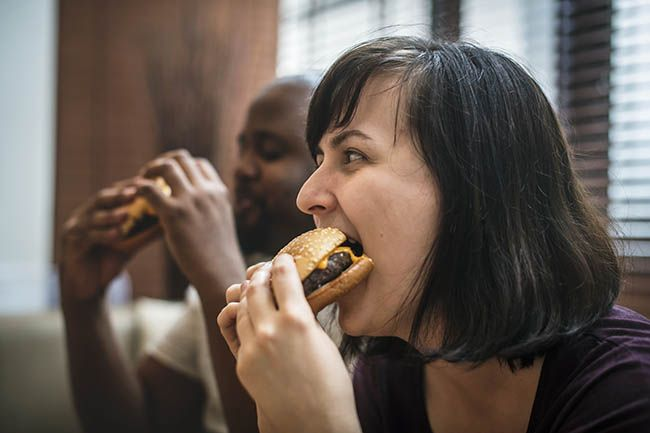 Couple having fast food, which can cause headaches, on the couch