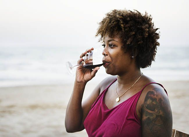 Woman drinking wine on the beach, common headache cause