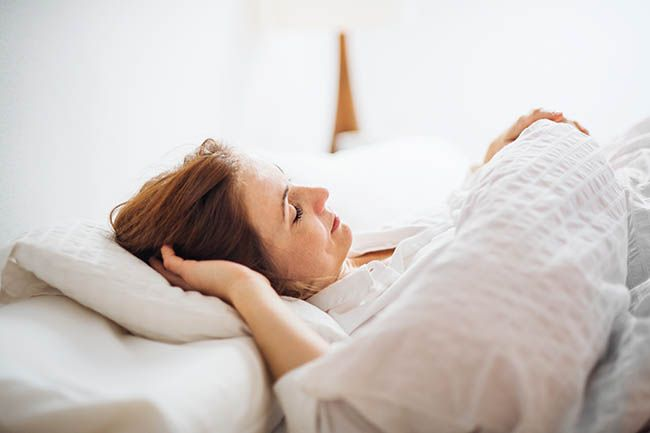 Woman comfortably going to sleep at night.