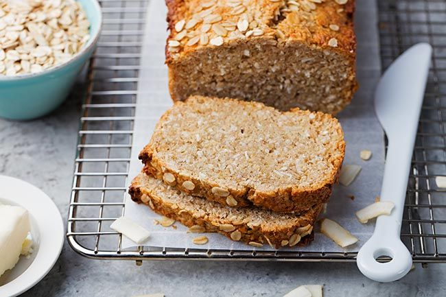 Healthy, gluten-free, vegan oat and coconut loaf bread on a cooling rack. Grey stone background