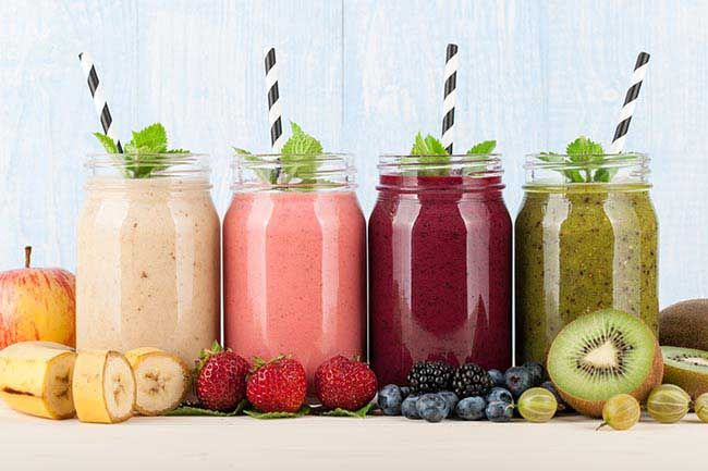 various smoothies, not keeping habit for gut health, fruits and berries on blue wooden background