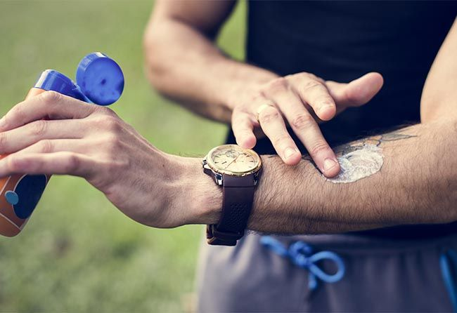 Man dressed in athletic clothes putting sunscreen on arm