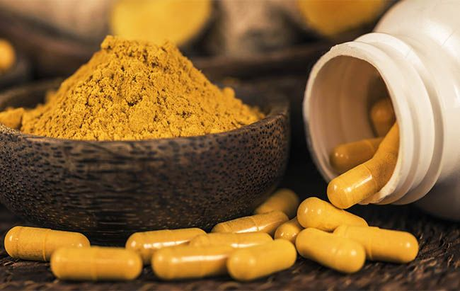 Curcumin herbal supplement capsules and turmeric powder in glass bowl. Anti-inflammatory herbal medicine (Curcuma)