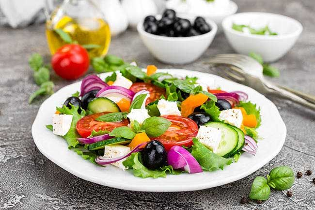 Greek salad. Fresh vegetable salad with tomato, onion, cucumbers, basil, pepper, olives, lettuce and feta cheese. olive oil behind plate.