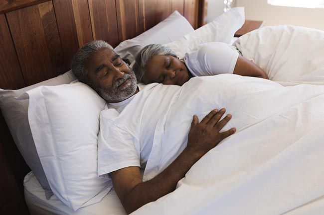 Close-up of a senior Indian couple sleeping together in bedroom at home