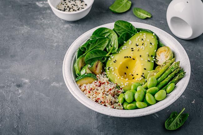 Healthy green vegetarian bowl lunch with grilled vegetables and quinoa, spinach, avocado, brussels sprouts, zucchini, asparagus, edamame beans with sesame seeds on dark gray background. Top view.