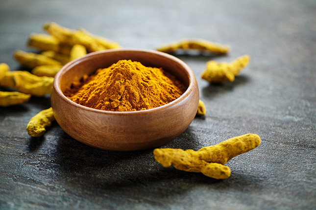 orange turmeric roots and powder in wooden bowl
