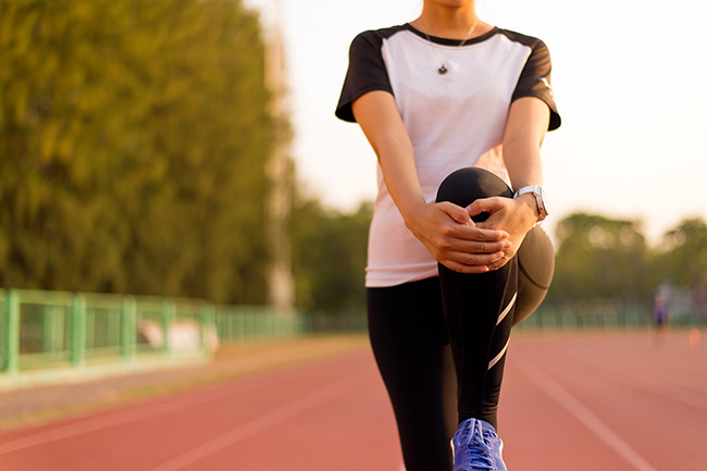 staying active is good for your joints. woman stretching knee on a walk.