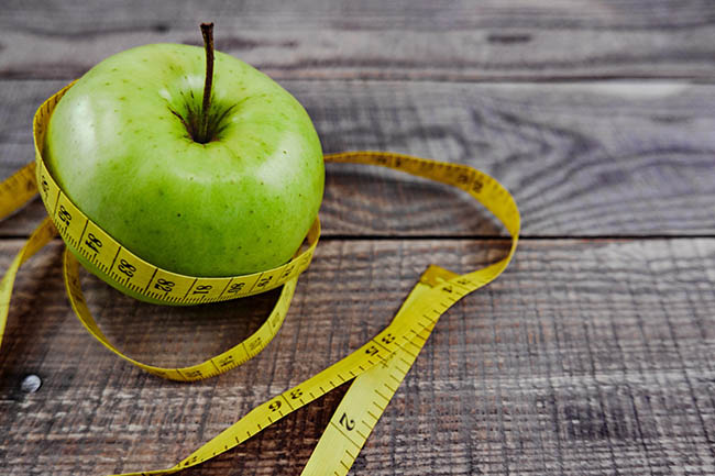 Tape measure and apple, the healthy benefits of eating well and losing weight.