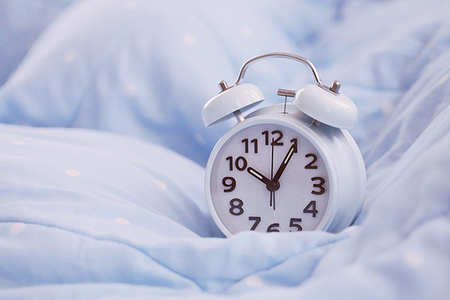 Clock on bed. Prioritizing sleep everynight can maintain energy throughout the day.