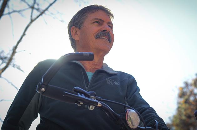 Dr. Bill Rawls riding his bike, smiling