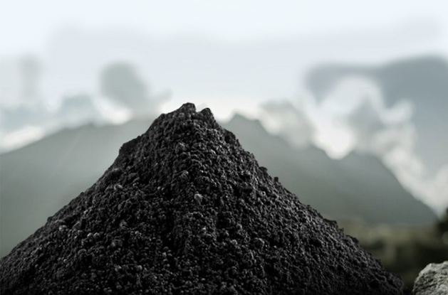 black shilajit powder pile in front of mountain view