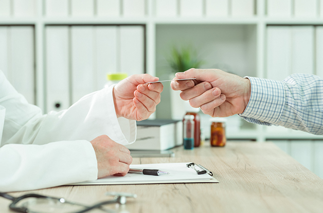 Doctor taking medical insurance card from patient in office during scheduled checkup